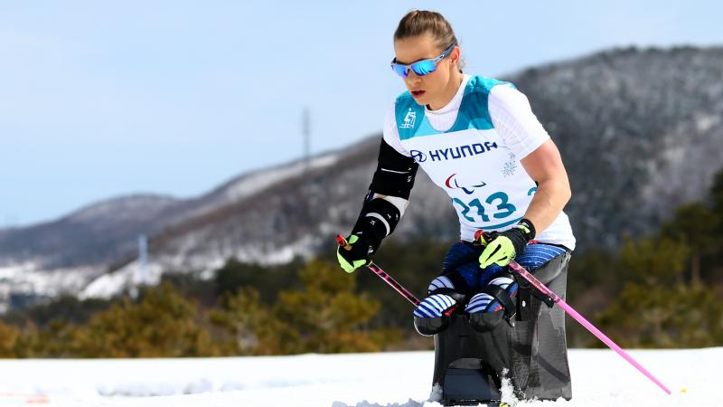 female sit skier Oksana Masters pushing through the snow