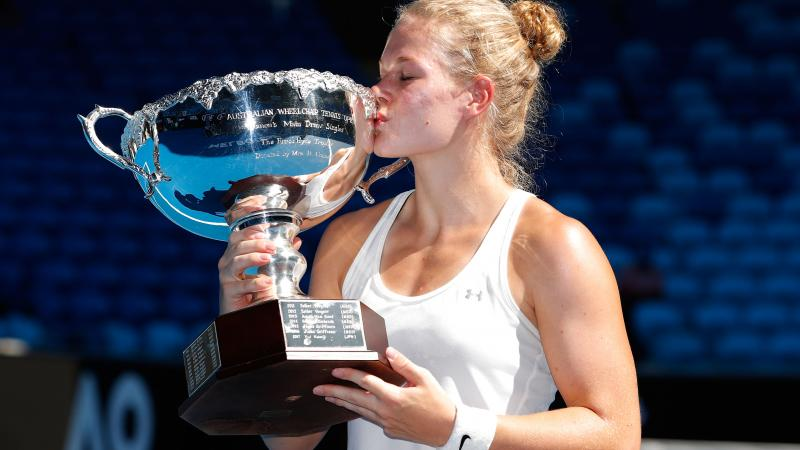 female wheelchair tennis player Diede de Groot holds up a trophy and kisses it