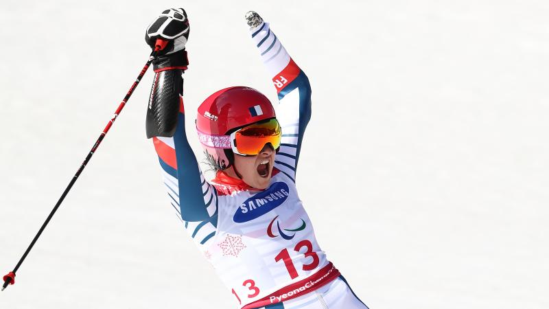 female Para alpine skier Marie Bochet raises her arms on the slopes after crossing the finish line