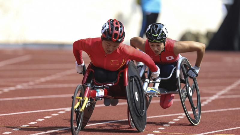 female wheelchair racer Hongzhuan Zhou rolls her wheels to stay ahead of a Japanese athlete