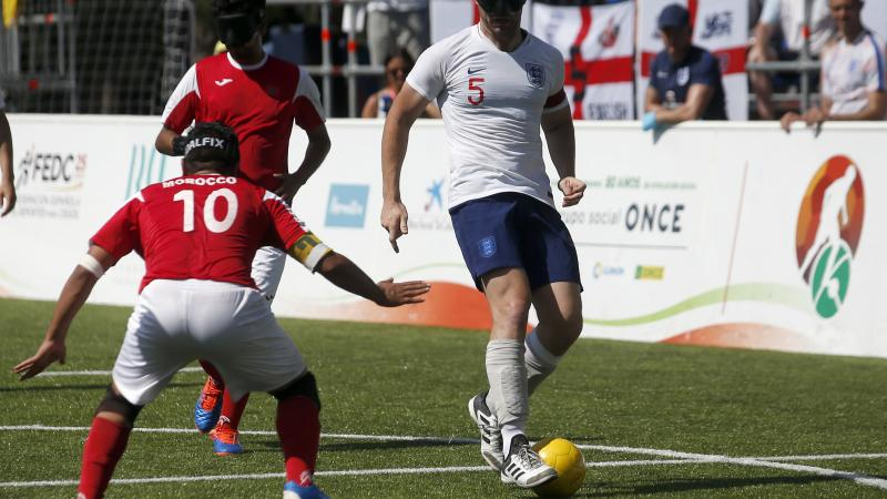 male blind footballer Dan English dribbles the ball past an opposition player