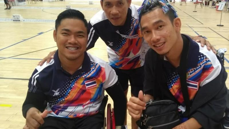 two Thai boccia players and their coach standing behind them and smiling with his arms around their shoulders