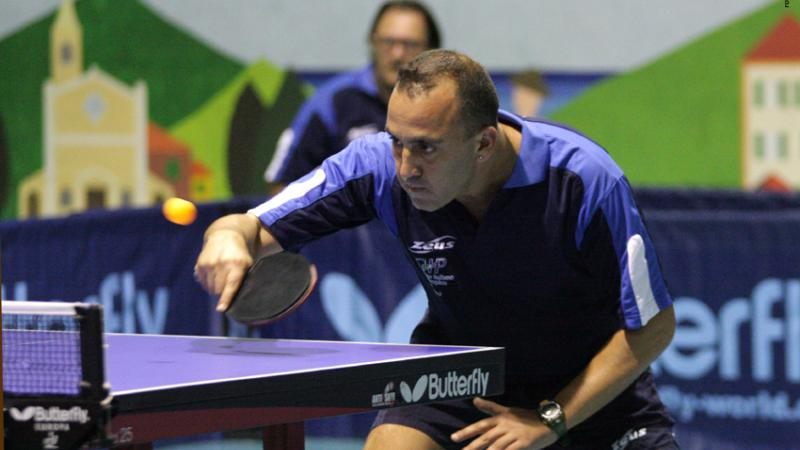 a male intellectually impaired table tennis player plays a backhand across the table