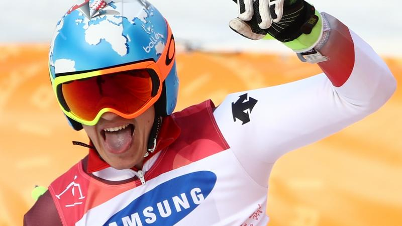 male Para alpine skiing Theo Gmur punches the air and smiles after crossing the finish line