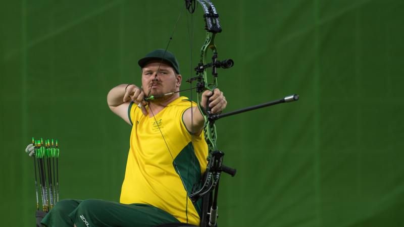 Australian male archer in wheelchair pulls back on his bow