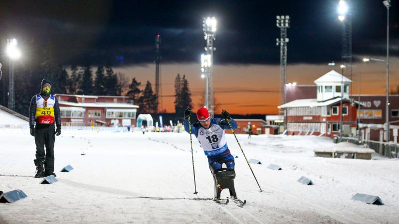 A man in a sitting ski competing in a biathlon race