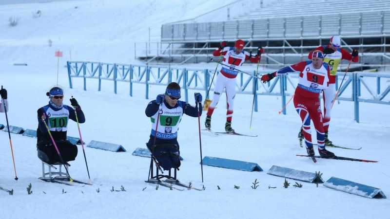 A group sitting and standing skiers competing in a Para biathlon race