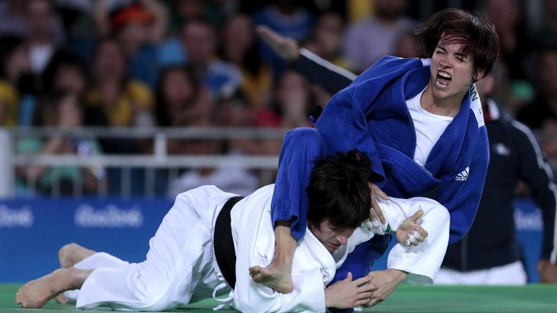 Female judoka Sandrine Martinet in a blue robe throws a judoka in a white robe onto the mat