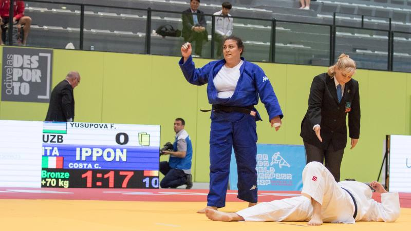 female judoka Carolina Costa stands over her opponent on the ground after winning the fight by ippon