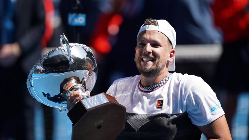 male wheelchair tennis player Dylan Alcott holds up a silver trophy and smiles