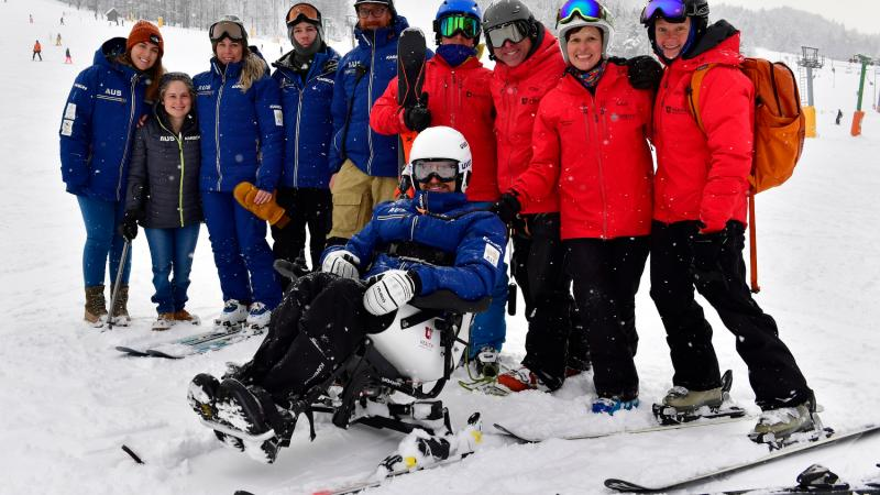 a group of skiing technical people standing behind a male Para alpine sit skier on the ski slope