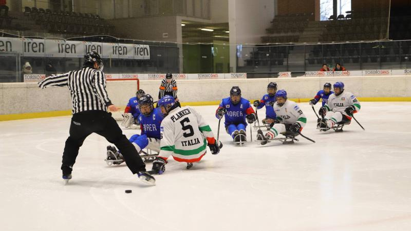 Two referees, three Italian and five South Korean Para ice hockey players on ice