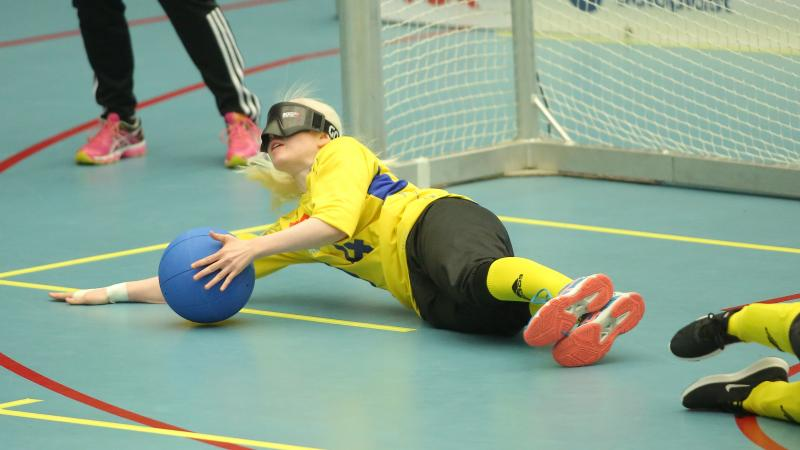 a female goalball player makes a save on the ground