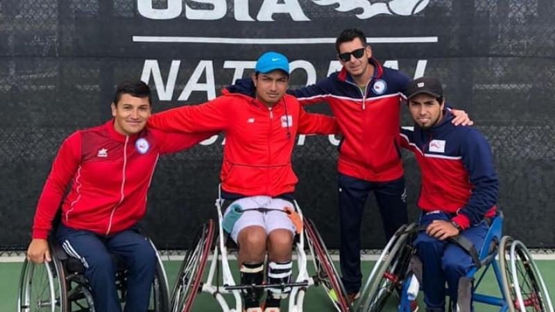 three male wheelchair tennis players and another man with their arms around eachother on a hard court
