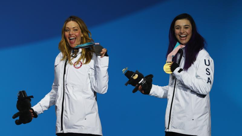 female Para snowboarders Amy Purdy and Brenna Huckaby holding up their medals and waving