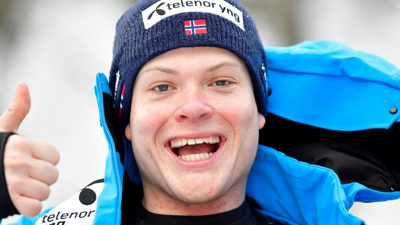 male Para alpine skier Jesper Pedersen smiles and gives a thumbs up to the camera