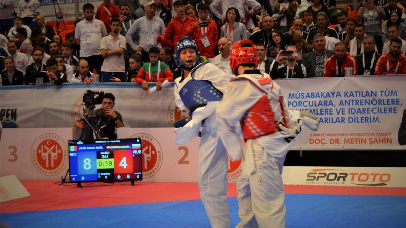 male Para taekwondo fighter Juan Garcia Lopez kicks another fighter around the back