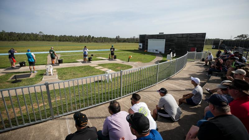 a wide shot of a sunny shooting range outside with athletes preparing to shoot