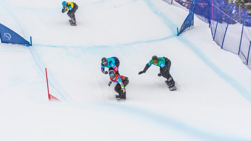 four male Para snowboarders racing on the snow with Alex Massie on the right