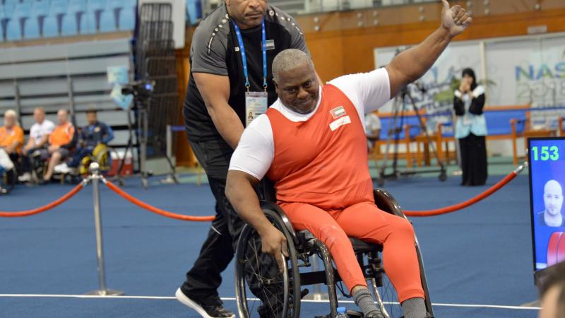 male Para powerlifter Mohammed Khamis Khalaf gives a thumbs up and smiles