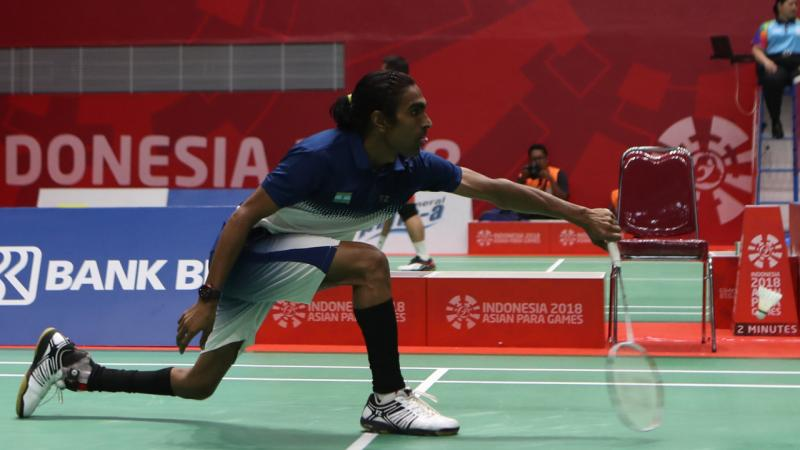 male Para badminton player Pramod Bhagat lunges to play a backhand