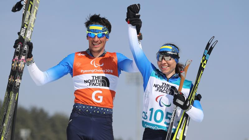 female Para Nordic skier Oksana Shyshkova holds hands with her guide as they raise their arms in victory