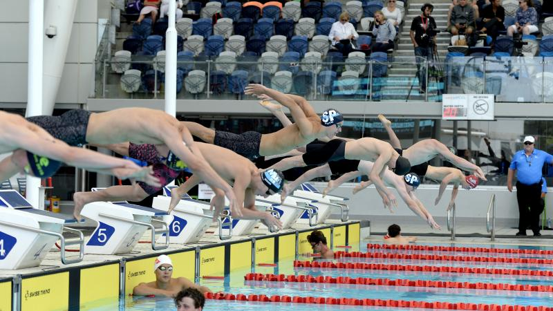 male Para swimmers diving into a pool at the start of the race in Melbourne