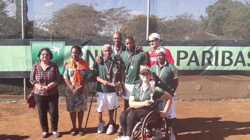 male and female wheelchair tennis players from South Africa hold up a trophy and smile