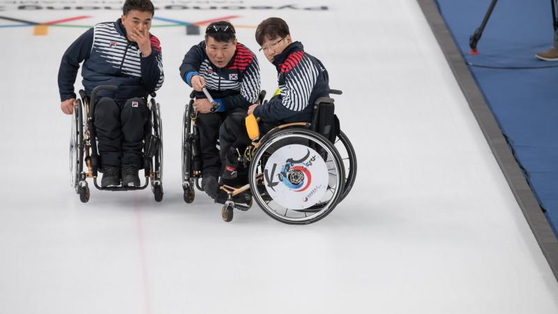 three male wheelchair curlers with Soon-Seok Seo on the right discussing how to play a stone