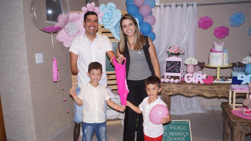 Paralympic swimmer Daniel Dias and his wife holding up a little pink swimsuit, with their two boys standing in front