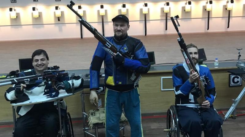 Three male medallists pose with their rifles