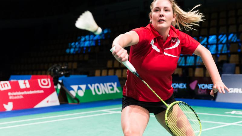 female Para badminton player Cathrine Rosengren reaches to play a backhand