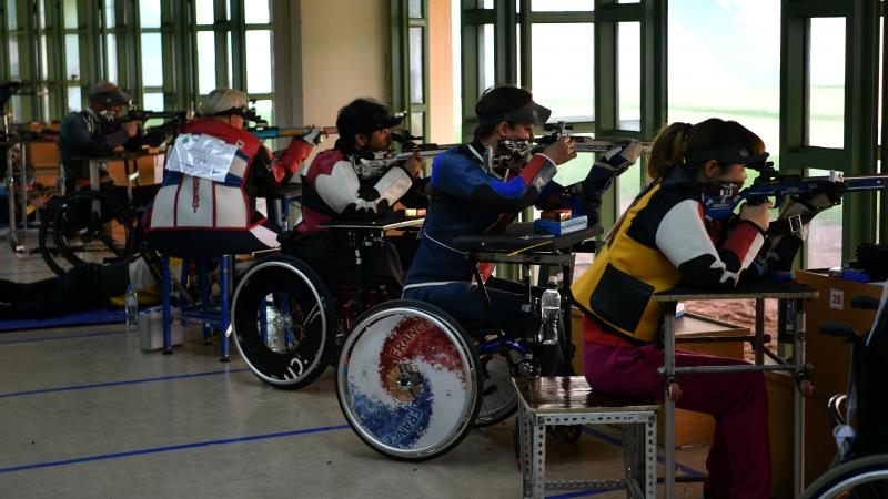 Para shooters sitting in wheelchairs firing rifles on the range