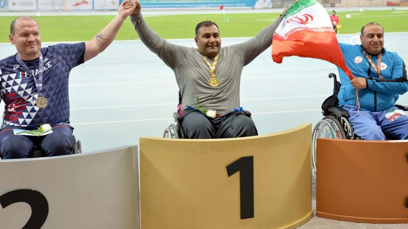 three male Para athletes in wheelchairs on the podium with Hamed Amiri in the centre holding an Iranian flag
