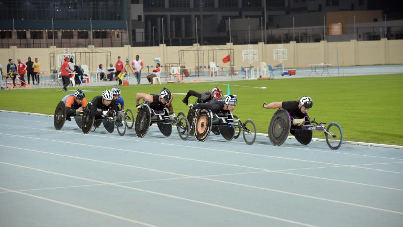 Group of men in racing chairs compete on a track