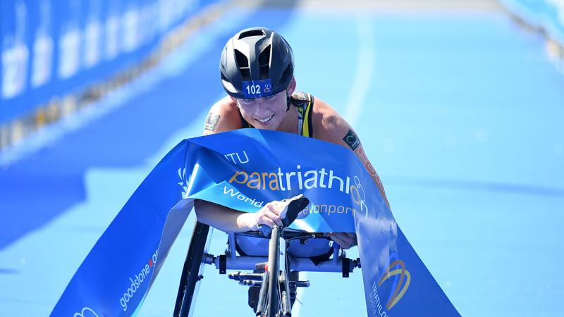 Australian woman in racing wheelchair crosses the finishline tape at a triathlon event