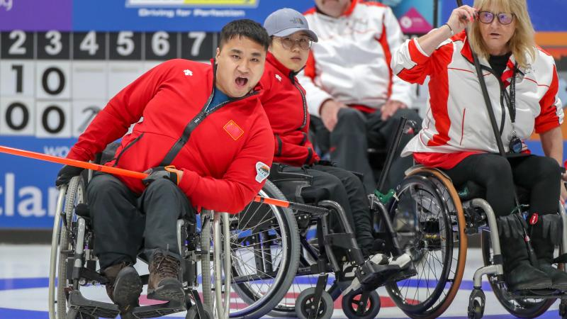 Chinese male wheelchair curler reacts as he releases his stone