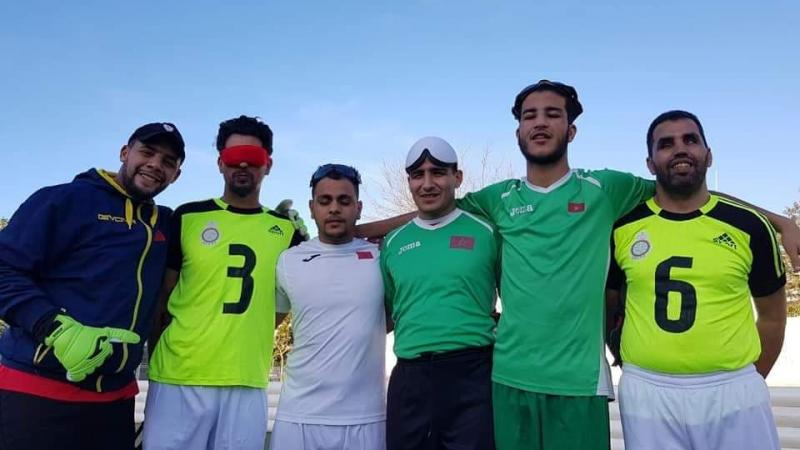 a group of five blind footballers from Oman smiling down at the camera