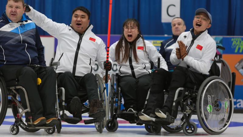 Three Chinese wheelchair curlers celebrate expressively on the ice
