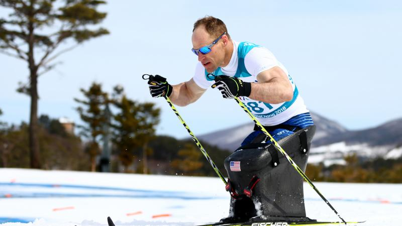 male Para Nordic sit skier Daniel Cnossen pushes through the snow