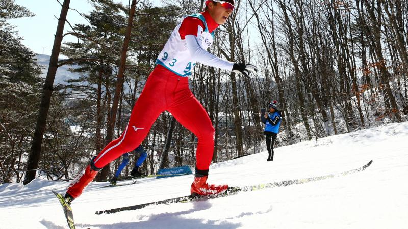 male Para Nordic skier Taiki Kawayoke skis through the forest