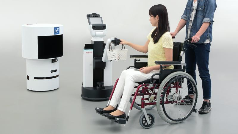 a person in a wheelchair having their basket held by a robot