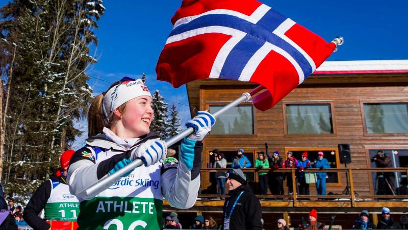 female Para Nordic skier Vilde Nilsen holds up a Norwegian flag