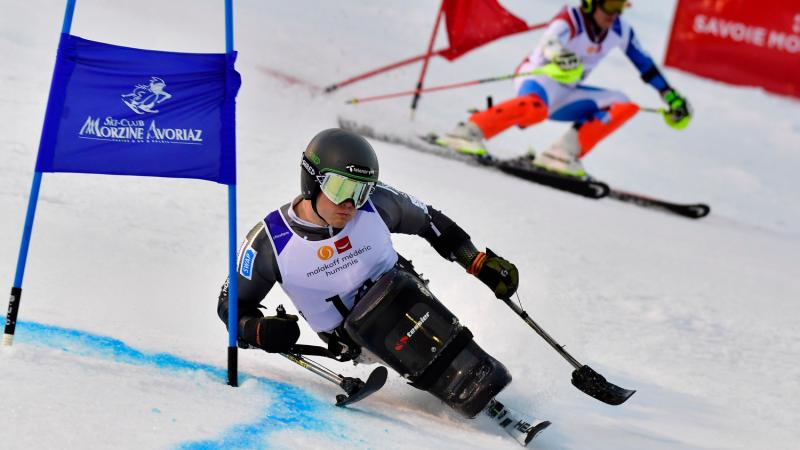 male sit skier Jesper Pedersen races head to head with a standing skier
