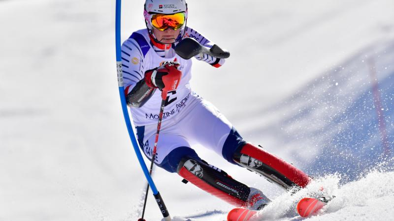 female Para alpine skier Marie Bochet turns through a gate