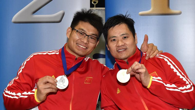male wheelchair fencers Hu Daoliang and Feng Yanke hold up their medals and smile