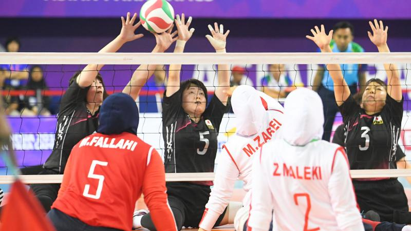 two female sitting volleyball teams contesting the ball on court