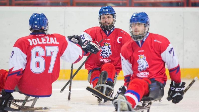 Three male Para ice hockey players on ice