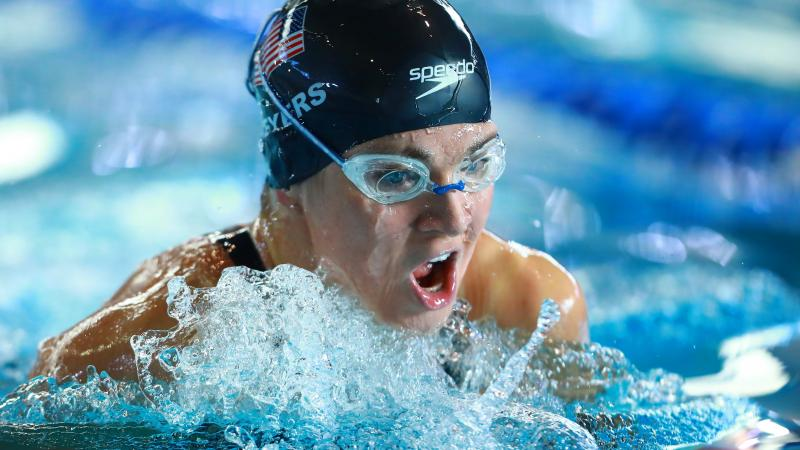 female Para swimmer Rebecca Meyers takes a breath mid-breaststroke