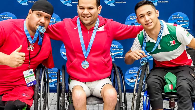 Three men in wheelchairs in a podium